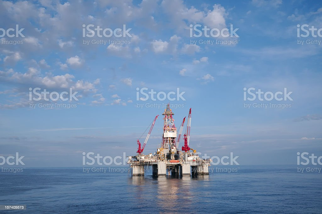 A deep water oil drilling platform at sea with calm waters and...