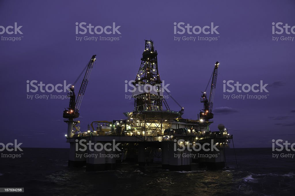 A deep water floating oil rig photographed at early dawn with lights...