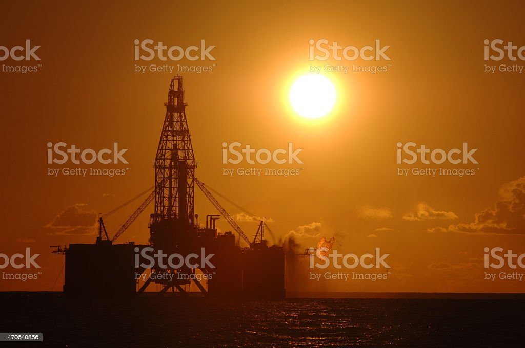 An oil rig situated in the ocean exploring for oil and gas. The rig...