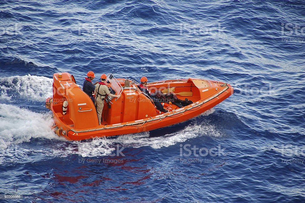 Ocean rescue team in bright orange boat stock photo
