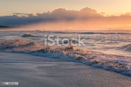 Ocean sandy beach with mild waves at sunrise. Beautiful summer nature scene background, wallpaper