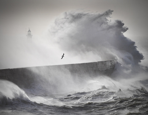 High winds churn the English channel causing huge waves over Newhaven harbour lighthouse