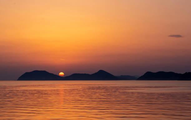 Ocean sunset over mountains stock photo