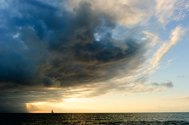 ocean sunset sailboat storm - storm stock photos and pictures
