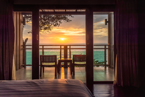 Ocean sunset view from bedroom balcony for travel concept.