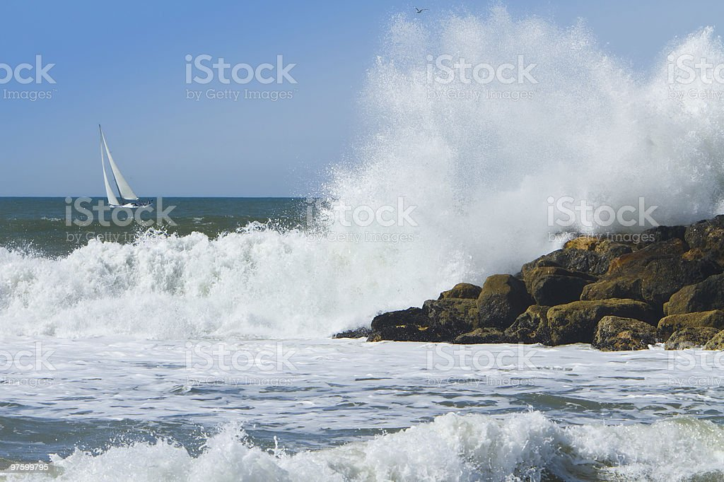 Ocean Surf Breaking Over Jetty With Sailboat royalty-free stock photo