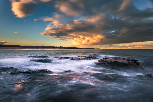 Ocean tide water flowing over rocks and with golden stormy sunset