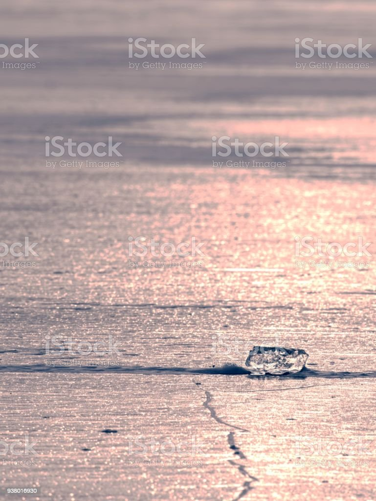 Ocean under transparent ice cover. The sun glare on the flat ice stock photo