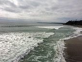 ocean view from pier with waves and cloudy ominous sky