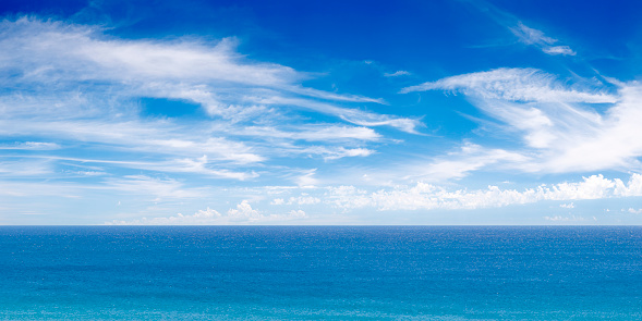 A stitched panorama of a vibrant blue ocean.