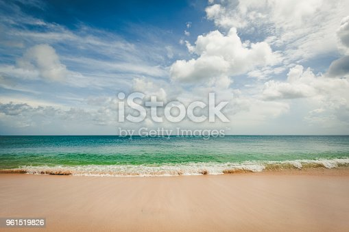tropical dream beach with dramatic sky horizon over water at bali island in indonesia.