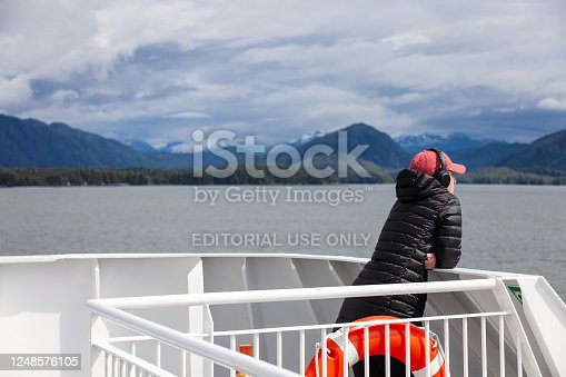 Port Edward, Canada - May 17, 2020. A person looks at the views of the coastline near Prince Rupert while standing on the deck of a boat.