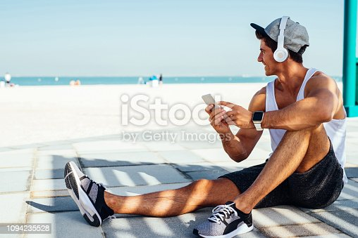 Shot of a smiling young man sitting outside and listening to the music while enjoying the view of the ocean.