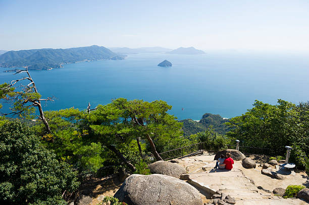 Ocean Views Couple taking in a stunning ocean view miyajima stock pictures, royalty-free photos & images