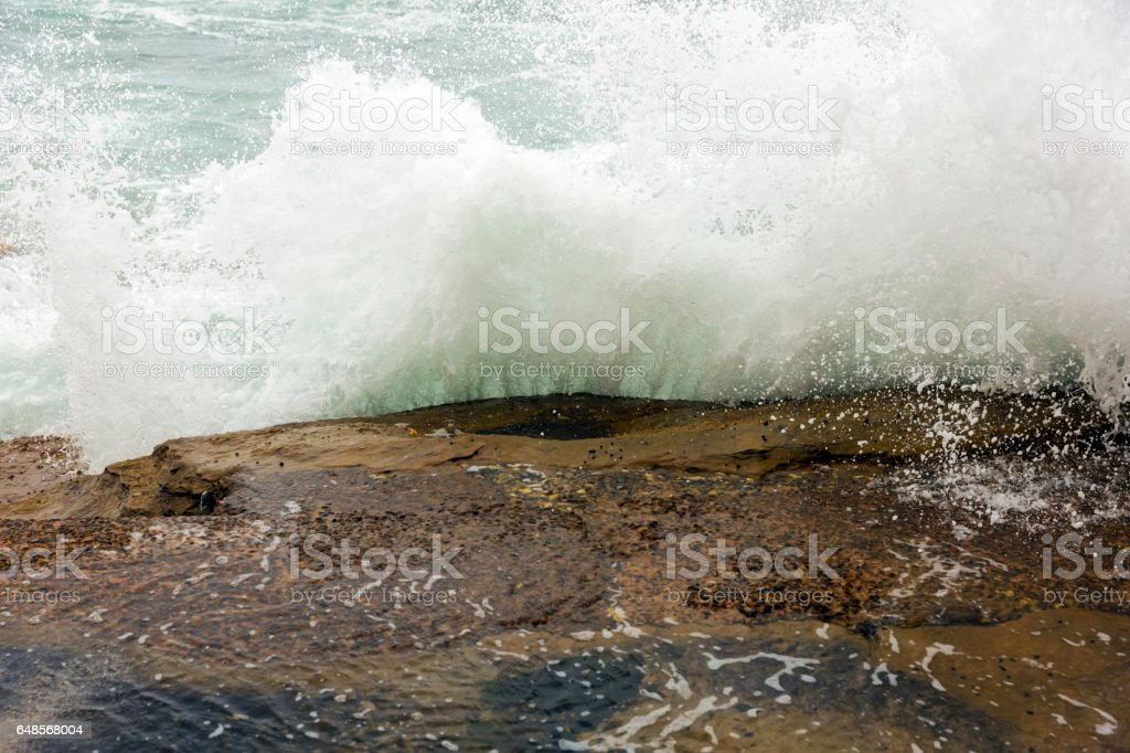 Ocean water spashing on the rock, background with copy space stock photo
