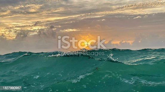 istock Ocean wave about to break at sunrise 1327990957
