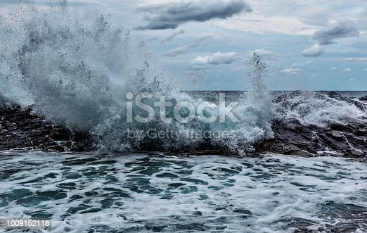 Ocean wave hitting against rocky barrier