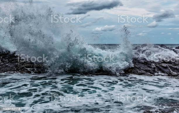 Photo of Ocean Wave Crashing into Rocks