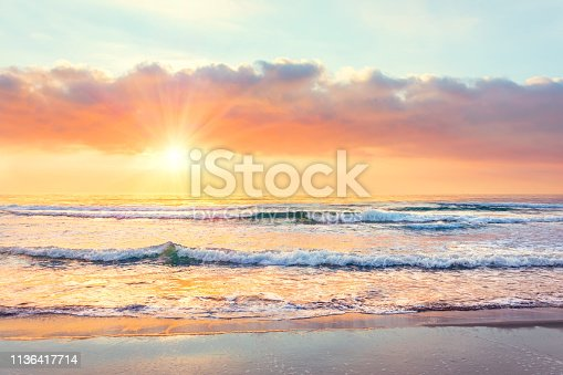 Ocean wave on the beach at sunset time, sun rays