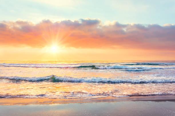 olas oceánicas en la playa al atardecer, rayos solares. - playa fotografías e imágenes de stock
