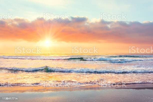 Photo of Ocean wave on the beach at sunset time, sun rays.