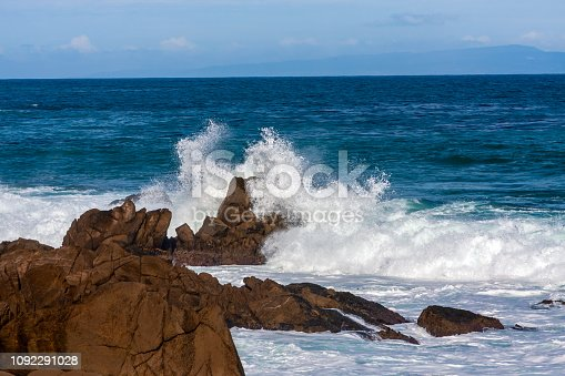 Ocean wave splashes against large rocks on shore in Monterey Bay, California