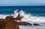 Ocean wave splashes against large rocks on shore in Monterey Bay, California