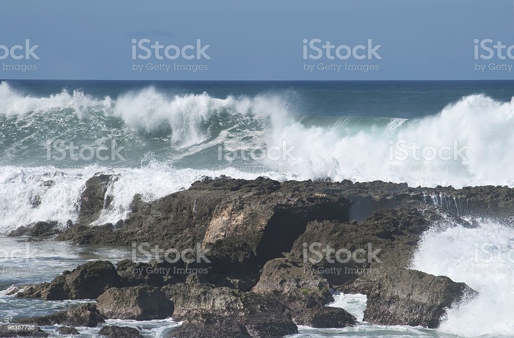 Ocean waves about to crash into volcanic rock royalty-free stock photo