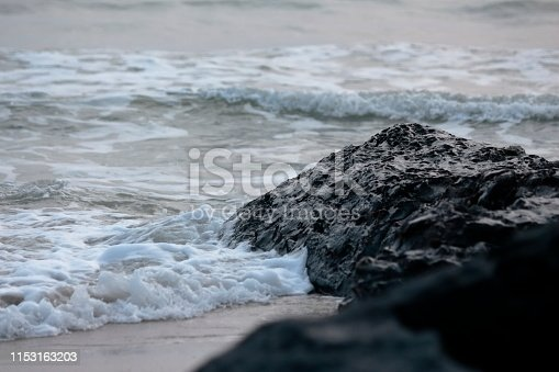 Waves hit the beach and black volcanic rocks