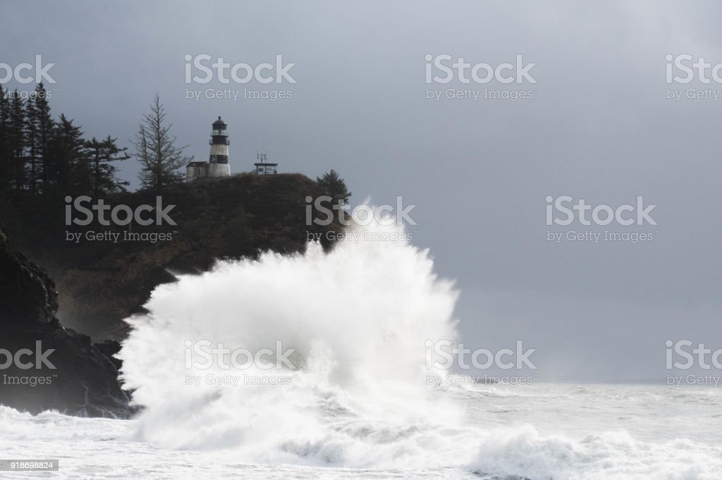 Ocean waves breaking on rocks below Cape Disappointment Lighthouse. stock photo