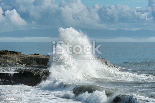 Large ocean waves crashing on rocky pacific shore.  Taken in Santa Cruz, California, USA