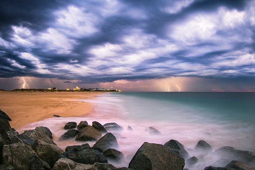 Ocean waves flowing over rocks and beach at sunset with storm clouds and lightning