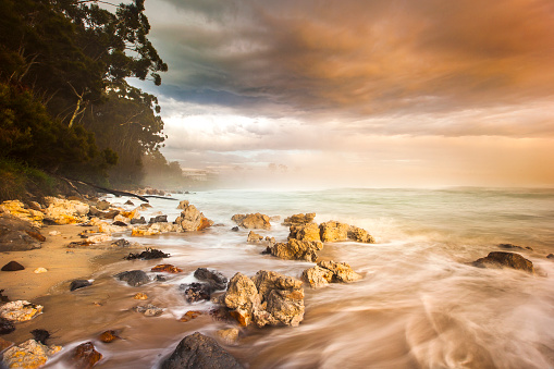 Ocean waves flowing over rocks at sunrise with orange and gold storm clouds