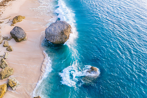 Ocean waves hitting a rocky beach. View from above.