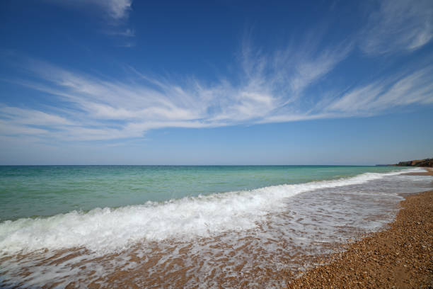 Oceanside under blue sky with clouds stock photo