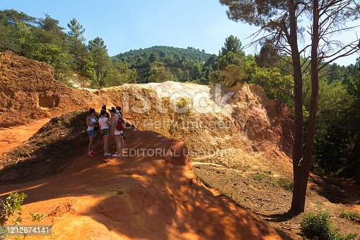 Roussilion,France-august 13,2016:tourists visiting the famous Ocra color quarries near Roussillon in France during a sunny day