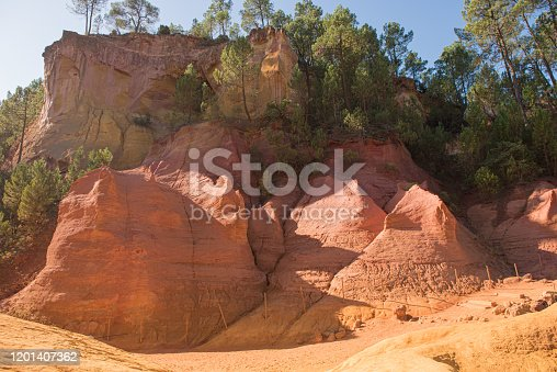 Ochre Trail in Roussillon, Sentier des Ocres, hiking path in a natural colorful area of red and yellow cliffs surrounded by green forest in Provence, Southern France