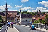 Ochsenfurt, Germany - May 31, 2019: Pedestrians and cyclists cross the new Main Bridge in Ochsenfurt at the Main.