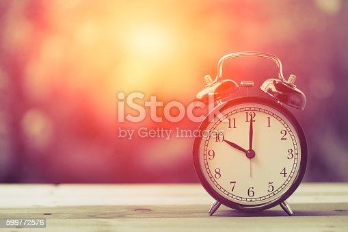 istock 10 o'clock Clock Vintage on Wood Table with Sun Light 599772576