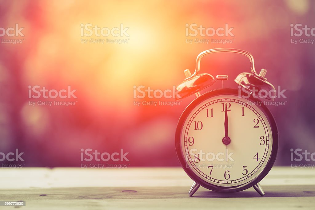 12 o'clock Clock Vintage on Wood Table with Sun Light stock photo