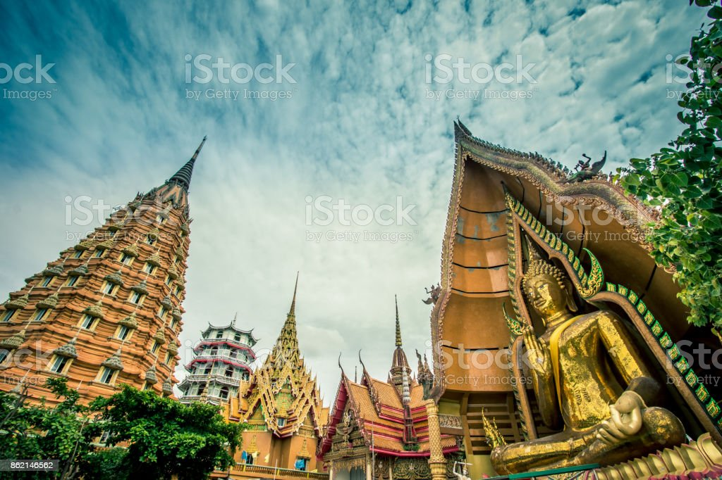 Octagonal pagoda,Chinese Pagoda,Vihara and large golden Buddha statue at Wat Tham Sua(Tiger Cave Temple),Tha Muang District,Kanchanaburi,Thailand. stock photo