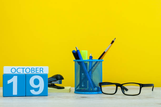 october 19th. day 19 of october month, wooden color calendar on teacher or student table, yellow background . autumn time - number 19 stock photos and pictures