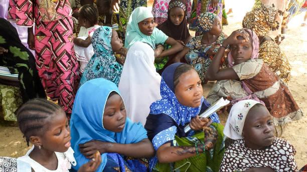 Oktober 2013 – Maradi, Niger: Islamitische schoolmeisjes krijgen van bescherming van de extreme hitte in Niger onder een schaduw van een boom, buiten hun school. foto
