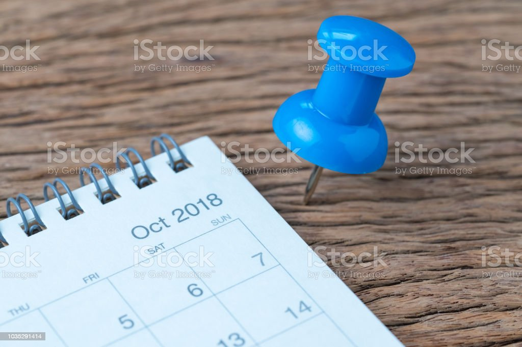 October 2018 calendar appointment, deadline, holiday or date planning concept, big blue pushpin or thumbtack pin on wooden table next to Sep white clean calendar stock photo