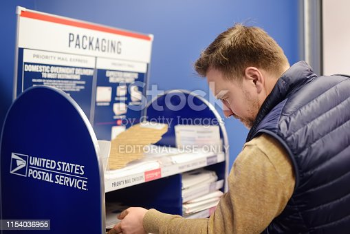 NEW YORK, USA - 23 october 2018: Mature man at the post office chooses an packaging - envelope or box for mailing. Postal system of the United States