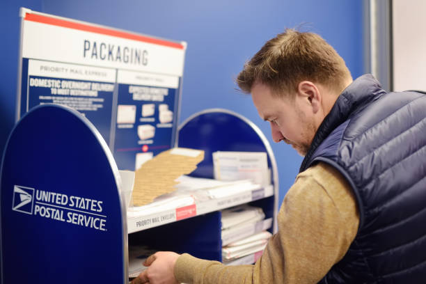 NEW YORK, USA - 23 october 2018: Mature man at the post office chooses an packaging - envelope / box for mailing. stock photo