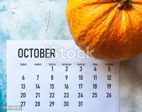 Simple 2019 October monthly calendar on table with a pumpkin