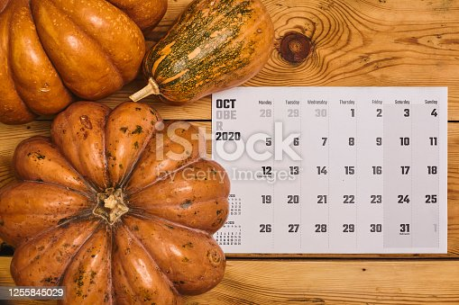 Simple 2020 October monthly calendar on the wooden desk with a pumpkin