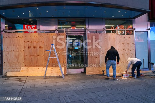 NEW YORK - October 31, 2020: Carpenters board up a storefront in Times Square in anticipation of unrest related to to the upcoming presidential election.