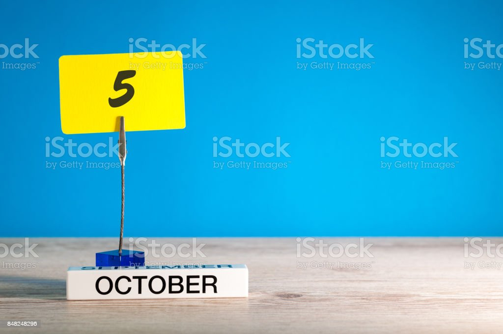 October 5th. Day 5 of october month, calendar on workplace with blue background. Autumn time. Empty space for text stock photo